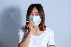 Jonge vrouwen rokende sigaret met beschermend masker Royalty-vrije Stock Afbeelding