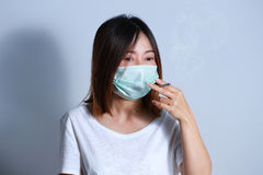 Jonge vrouwen rokende sigaret met beschermend masker Royalty-vrije Stock Foto's