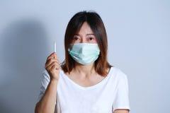 Jonge vrouwen rokende sigaret met beschermend masker Stock Afbeeldingen