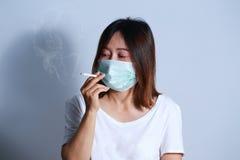 Jonge vrouwen rokende sigaret met beschermend masker Royalty-vrije Stock Foto