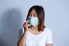 Jonge vrouwen rokende sigaret met beschermend masker Royalty-vrije Stock Afbeeldingen