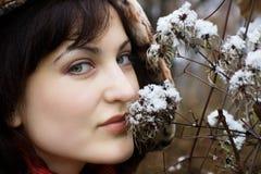 Jonge vrouwen ruikende bloem met sneeuw Stock Foto
