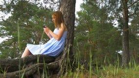 Jonge vrouwen` s hand wat betreft smartphone op het groene gras - Zonsondergangeffect effect stock videobeelden