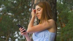 Jonge vrouwen` s hand wat betreft smartphone op het groene gras - Zonsondergangeffect effect stock footage