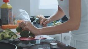 Jonge vrouwen scherpe brocoli bij binnenlandse keuken stock footage