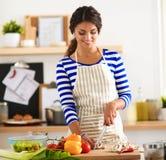 Jonge vrouwen scherpe groenten in keuken Stock Afbeeldingen