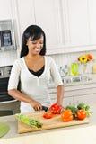 Jonge vrouwen scherpe groenten in keuken Royalty-vrije Stock Foto