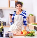 Jonge vrouwen scherpe groenten in keuken, holding een glas wijn Stock Foto