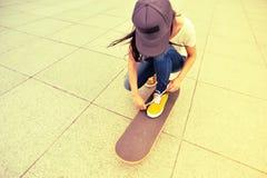 Jonge vrouwen skateboarder bindende schoenveter Royalty-vrije Stock Foto