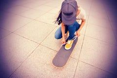 Jonge vrouwen skateboarder bindende schoenveter Royalty-vrije Stock Afbeelding