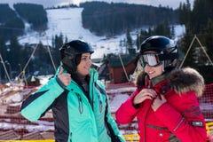 Jonge vrouwen in skikostuums, met helmen en van skibeschermende brillen status stock foto