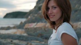 Jonge vrouwen stellende zitting op strand in de zomeravond in openlucht stock video