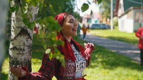 Jonge vrouwen in traditionele Russische kleding die zich onder de berk boom en het zingen bevinden stock video