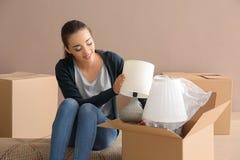Jonge vrouwen uitpakkende doos binnen Het bewegen zich in Nieuw Huis royalty-vrije stock foto