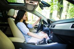 Jonge vrouwen veranderende toestellen in auto Het drijven van een mening Car royalty-vrije stock afbeeldingen