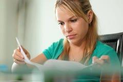 Jonge vrouwen vrouwelijke student die thuis bestuderen Stock Afbeeldingen