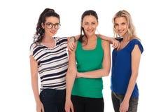 3 jonge vrouwen zich en glimlach die verenigen Stock Afbeeldingen