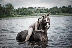 Jonge vrouwen zwemmende hengst binnen in rivier Royalty-vrije Stock Fotografie