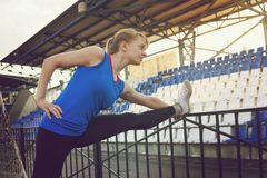 Jonge vrouwenagent het uitrekken zich benen vóór looppas tijdens zonnige ochtend op stadionspoor Agentvrouw het uitrekken zich vó stock foto's