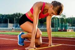 Jonge vrouwenatleet bij beginnende positie klaar om een race op renbaan te beginnen Royalty-vrije Stock Afbeeldingen
