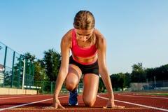 Jonge vrouwenatleet bij beginnende positie klaar om een race op renbaan te beginnen Stock Afbeelding