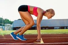 Jonge vrouwenatleet bij beginnende positie klaar om een race op renbaan te beginnen Stock Afbeeldingen