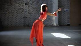 Jonge vrouwenballerina die in oranje kleding elegant prestaties maken stock footage