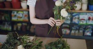 Jonge vrouwenbloemist die mooie bloemen schikken die samenstelling in winkel maken stock video
