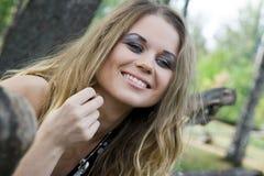 Jonge vrouwenblonde op achtergrondbomen in een park Stock Afbeeldingen