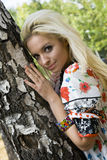Jonge vrouwenblonde op achtergrondbomen in een park Stock Afbeelding