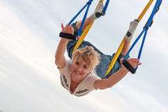 Jonge vrouwenbovenkant - onderaan het doen van anti-gravity luchtyoga of vlieg-yoga in hangmat op hemelachtergrond Royalty-vrije Stock Foto's