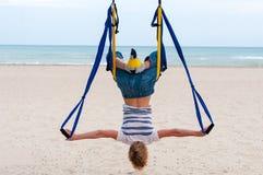 Jonge vrouwenbovenkant - onderaan het doen van anti-gravity luchtyoga of vlieg-yoga in hangmat op overzeese achtergrond Stock Fotografie
