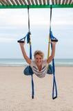 Jonge vrouwenbovenkant - onderaan het doen van anti-gravity luchtyoga of vlieg-yoga in hangmat op overzeese achtergrond Royalty-vrije Stock Fotografie