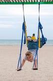 Jonge vrouwenbovenkant - onderaan het doen van anti-gravity luchtyoga of vlieg-yoga in hangmat op overzeese achtergrond Stock Afbeeldingen