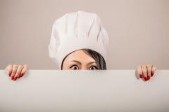 Jonge vrouwenchef-kok die een leeg wit teken houden Royalty-vrije Stock Foto