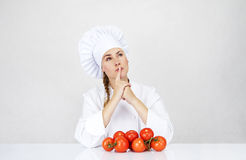 Jonge vrouwenchef-kok die ingrediënten voor Italiaans voedsel op wit tonen Stock Afbeelding