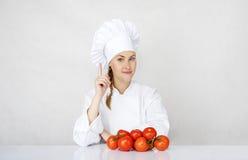 Jonge vrouwenchef-kok die ingrediënten voor Italiaans voedsel op wit tonen Royalty-vrije Stock Fotografie