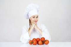 Jonge vrouwenchef-kok die tomaten voor Italiaans voedsel op wit tonen Stock Afbeeldingen