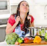 Jonge vrouwenchef-kok die zich over ketel die het koken van voedsel bevinden, haar eigen haar in frustratie en verstoorde gelaats royalty-vrije stock fotografie