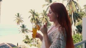 Jonge vrouwendranken vers op het hotelterras met oceaanmening stock videobeelden