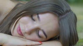 Jonge vrouwendromen die in park liggen die mooie vrouwelijke donkerbruine openlucht overwegen stock footage