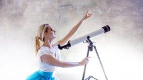Jonge vrouwendromen van de toekomst, concept Het meisje in de hemel met wolken kijkt omhooggaand en gebruikt een telescoop stock foto