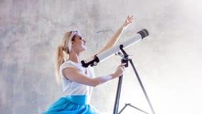 Jonge vrouwendromen van de toekomst, concept Het meisje in de hemel met wolken kijkt omhooggaand en gebruikt een telescoop stock afbeeldingen