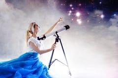 Jonge vrouwendromen van de toekomst, concept Het meisje kijkt omhooggaand en gebruikt een telescoop Sterrige hemel achter de wolk royalty-vrije stock foto's