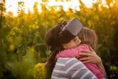Jonge vrouwenervaring met virtuele werkelijkheid Het koesteren van haar dochter met liefde Royalty-vrije Stock Afbeelding