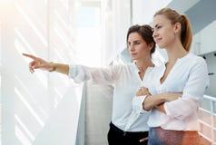 Jonge vrouwenfinancier die iets tonen aan haar partner door het bureauvenster terwijl status in gang, Royalty-vrije Stock Foto