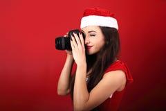 Jonge vrouwenfoto die de foto op rode achtergrond maken holdin Royalty-vrije Stock Afbeeldingen
