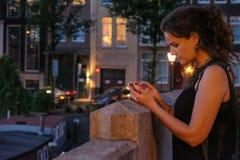 Jonge vrouwenfotograaf met smartphone op een brug royalty-vrije stock afbeelding