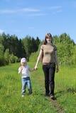 Jonge vrouwengangen met dochter dichtbij groen bos stock afbeelding