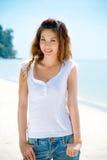 Jonge vrouwenglimlachen door het strand royalty-vrije stock afbeeldingen